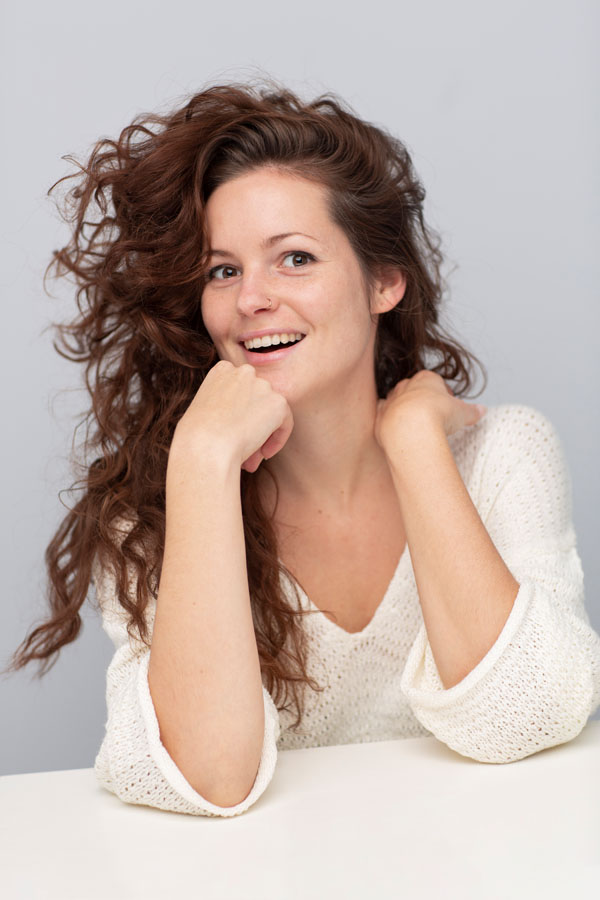 fotoshoot vrouw krullend haar lach belichte ruimte