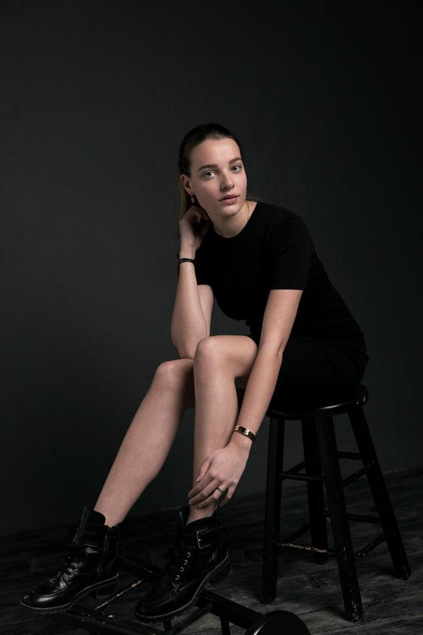 fotoshoot zittende vrouw zwarte kleding in donkere ruimte