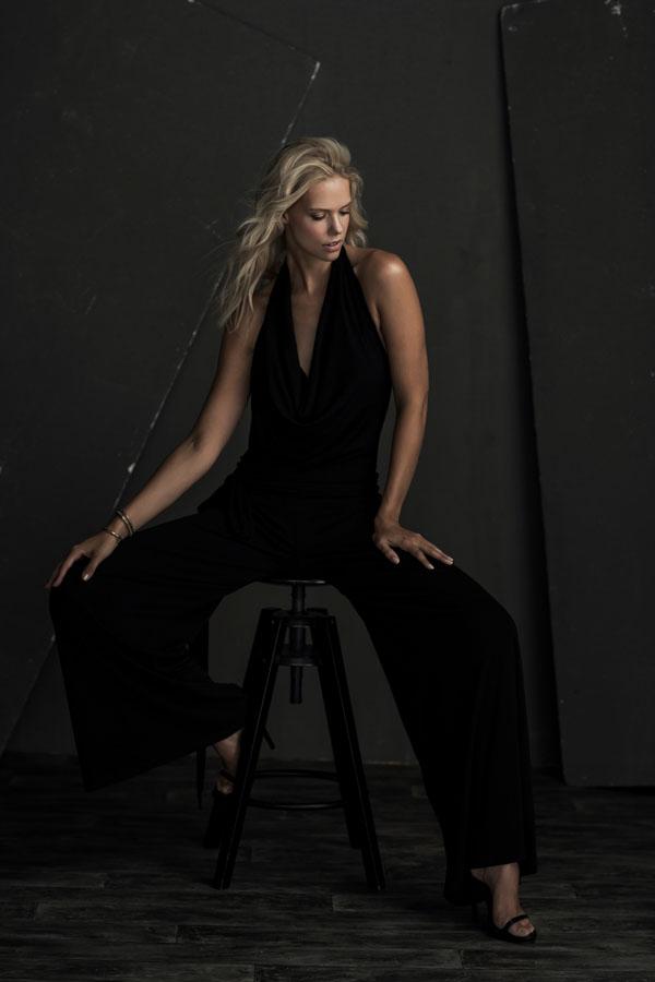 glamour fotoshoot vrouw zitten kruk donkere ruimte