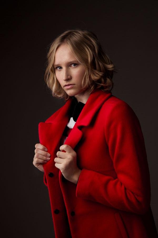 portret fotoshoot model in donker met rode jas