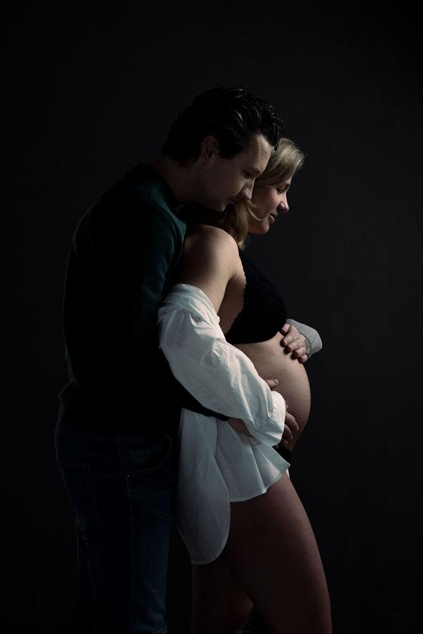 zwangerschap fotoshoot met partner donkere ruimte