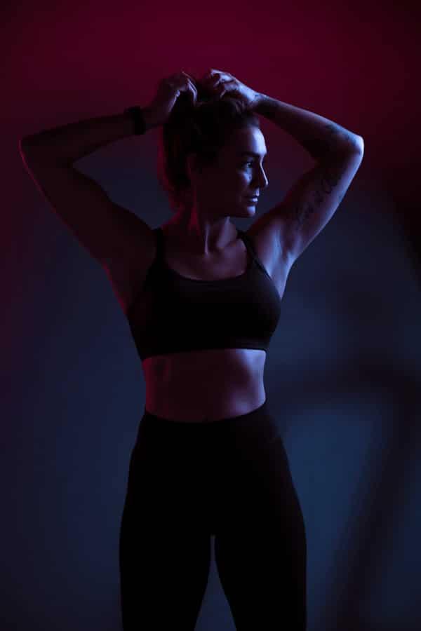 Sport fotoshoot jonge vrouw kleurrijke belichting